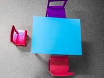 As tabelas e as cadeiras pequenas perto do quadro-negro na parede nas crianças batem foto de stock