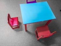 As tabelas e as cadeiras pequenas perto do quadro-negro na parede nas crian?as batem fotos de stock royalty free