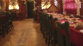 As tabelas prontos ajustaram-se em um restaurante para comemorar uma celebração, um aperitivo video estoque