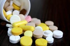 As tabuletas da medicamentação são soçobradas na tabela fotos de stock