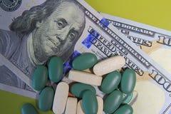 As tabuletas são dispersadas para dólares Conceito do dinheiro de droga fotografia de stock