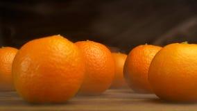 As tangerinas suculentas encontram-se em uma tabela de madeira em um fundo preto do que frescor e frescura gelados venha, 4K filme