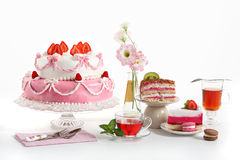 As it is tasty - party!. Luxory composition with a pie, tea, fruit cakes and flowers. Sweets from a confectioner's shop on a birthday party royalty free stock image