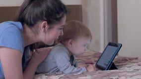 As tecnologias da educação, bebê curioso com mamãe feliz têm o divertimento com a tabuleta digital que encontra-se na cama na sal filme
