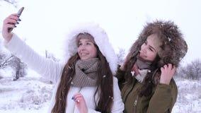 As tecnologias modernas, amigas fazem um beijo do ar para fotos no dispositivo no tempo de inverno video estoque