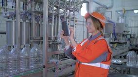 As tecnologias modernas na produção, mulher feliz do especialista da fábrica no capacete de segurança usam o portátil da tabuleta video estoque