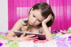As tecnologias tornam-se mais fáceis Menina bonito que guarda a tabuleta digital imagem de stock