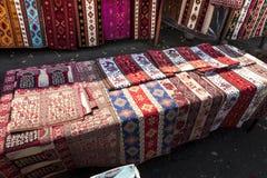 As telas coloridas e outros produtos populares em uma borda da estrada param a sagacidade Imagens de Stock