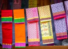 As telas e os xailes coloridos em um mercado param foto de stock