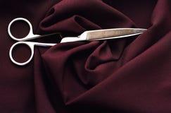 As tesouras do aço na tela de Borgonha Imagem de Stock Royalty Free
