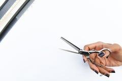 As tesouras do cabelo no isolado das mãos no fundo Fotografia de Stock Royalty Free