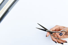 As tesouras do cabelo no isolado das mãos no fundo Fotos de Stock Royalty Free