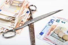 As tesouras monetárias vêm distante Fotografia de Stock Royalty Free