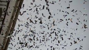 As tiras do espelho dos confetes caem na rua contra o céu filme