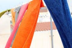 As toalhas coloridas são penduradas e movidas pelo vento Fotografia de Stock