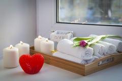 As toalhas de mão roladas em uma bandeja ao lado das velas iluminadas e em um ramalhete das tulipas no salão de beleza dos termas Fotos de Stock