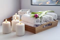 As toalhas de mão roladas em uma bandeja ao lado das velas iluminadas e em um ramalhete das tulipas no salão de beleza dos termas Imagens de Stock