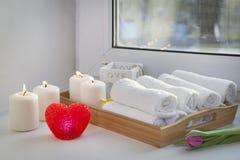 As toalhas de mão roladas em uma bandeja ao lado das velas iluminadas e em um ramalhete das tulipas no salão de beleza dos termas Imagens de Stock Royalty Free