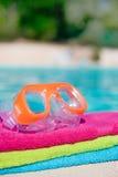 As toalhas e os óculos de proteção aproximam a piscina Imagens de Stock Royalty Free