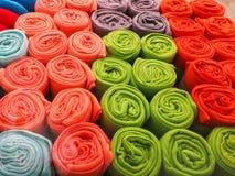 as toalhas Multi-coloridas rolaram em uma mentira do tubo em se na prateleira a tela Multi-colorida rolou em um tubo imagem de stock royalty free