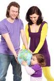 As tomadas da família olham com o globo pequeno do interesse fotografia de stock royalty free