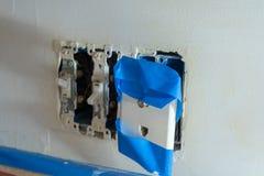 As tomadas elétricas interruptor da luz, o jaque de telefone e o cabo cobertos na fita dos pintores com as tampas removeram, devi foto de stock