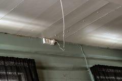 As tomadas elétricas montaram em uma parede de madeira gasta rústica velha com um cabo de poder fraco que pendura do teto e imagem de stock royalty free