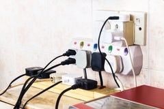 As tomadas múltiplas da eletricidade no adaptador arriscam sobrecarregar e dange fotografia de stock