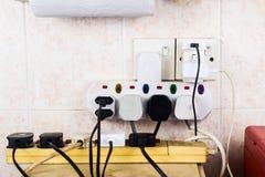 As tomadas múltiplas da eletricidade no adaptador arriscam sobrecarregar e dange fotografia de stock royalty free