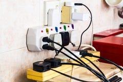 As tomadas múltiplas da eletricidade no adaptador arriscam sobrecarregar e dange imagem de stock