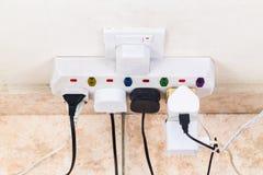 As tomadas múltiplas da eletricidade unidas ao multi adaptador são dangerou fotos de stock
