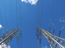 As torres e os fios de alta tensão contra o céu azul no parque aterram Foto de Stock