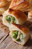 As tortas da massa folhada com ervilhas verdes fecham-se acima do vertical Imagem de Stock Royalty Free