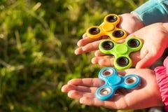 As três mãos das crianças mantêm os giradores unidos fotos de stock
