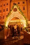 As três meninas estão tendo o divertimento sob a porta do Natal na praça da cidade velha foto de stock royalty free