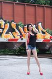 As the train goes rushing bye. Model at a pedestrian railroad crosswalk, train in background Stock Photo