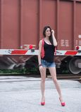 As the train goes rushing bye. Model at a pedestrian railroad crosswalk, train in background Stock Images