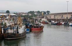 As traineiras usadas e vestidas do poço amarraram no porto de pesca ocupado de Kilkeel no condado Dow Ireland Fotos de Stock
