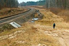 As trilhas de estrada de ferro, estrada de terra ao longo da estrada de ferro, ciclistas dos povos vão na estrada enlameada perto foto de stock royalty free
