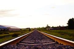 As trilhas Railway nos campos com as vilas intensas do workIn perderam usando o tempo passado do technologiesin Fotos de Stock