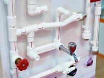 As tubulações e o metal plásticos do encanamento batem na exposição Imagem de Stock Royalty Free