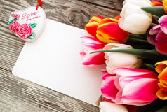 As tulipas ajuntam-se no fundo de madeira das pranchas do celeiro escuro Fotografia de Stock