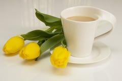 As tulipas amarelas encontram-se perto do copo do cappuccino Imagem de Stock