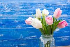 As tulipas coloridas florescem no fundo de madeira azul da tabela da mesa Copie o espaço Foto de Stock