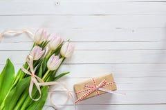 As tulipas cor-de-rosa com fita rosado e as caixas de presente em um branco pintaram w imagens de stock