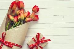 As tulipas e a caixa de presente vermelhas com fita vermelha em um branco pintaram o woode fotos de stock royalty free
