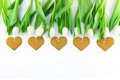 As tulipas e o coração brancos deram forma a cookies no fundo branco com espaço da cópia Dia da mola, de mãe ou conceito da Pásco imagem de stock