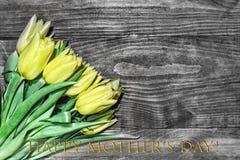 As tulipas felizes do amarelo do dia do ` s da mãe, fundo de madeira, denominam noir Fotografia de Stock