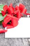 As tulipas vermelhas desvanecidas no carvalho bronzeiam a tabela com a folha branca do pape Fotografia de Stock Royalty Free
