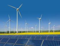 As turbinas de vento e os painéis solares em um rapeseed colocam Fotografia de Stock